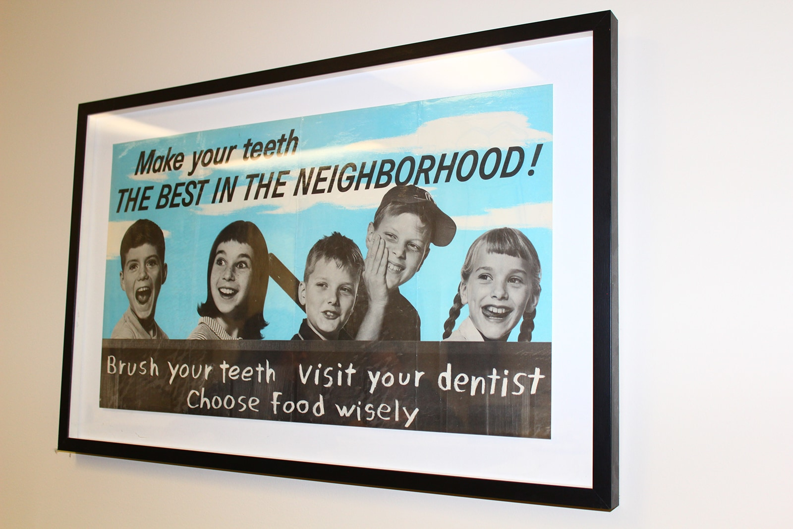 Picture of 5 kids that says make your teeth the best in the neighborhood! Brush your teeth, visit your dentist, choose food wisely hanging on a wall at Encino Cosmetic Dentistry.