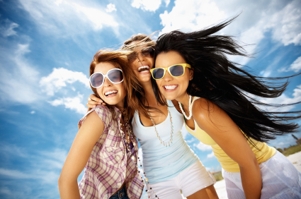 Three pretty woman with sun tans wearing sunglasses-smiling and hugging beneath a beautiful blue sky.