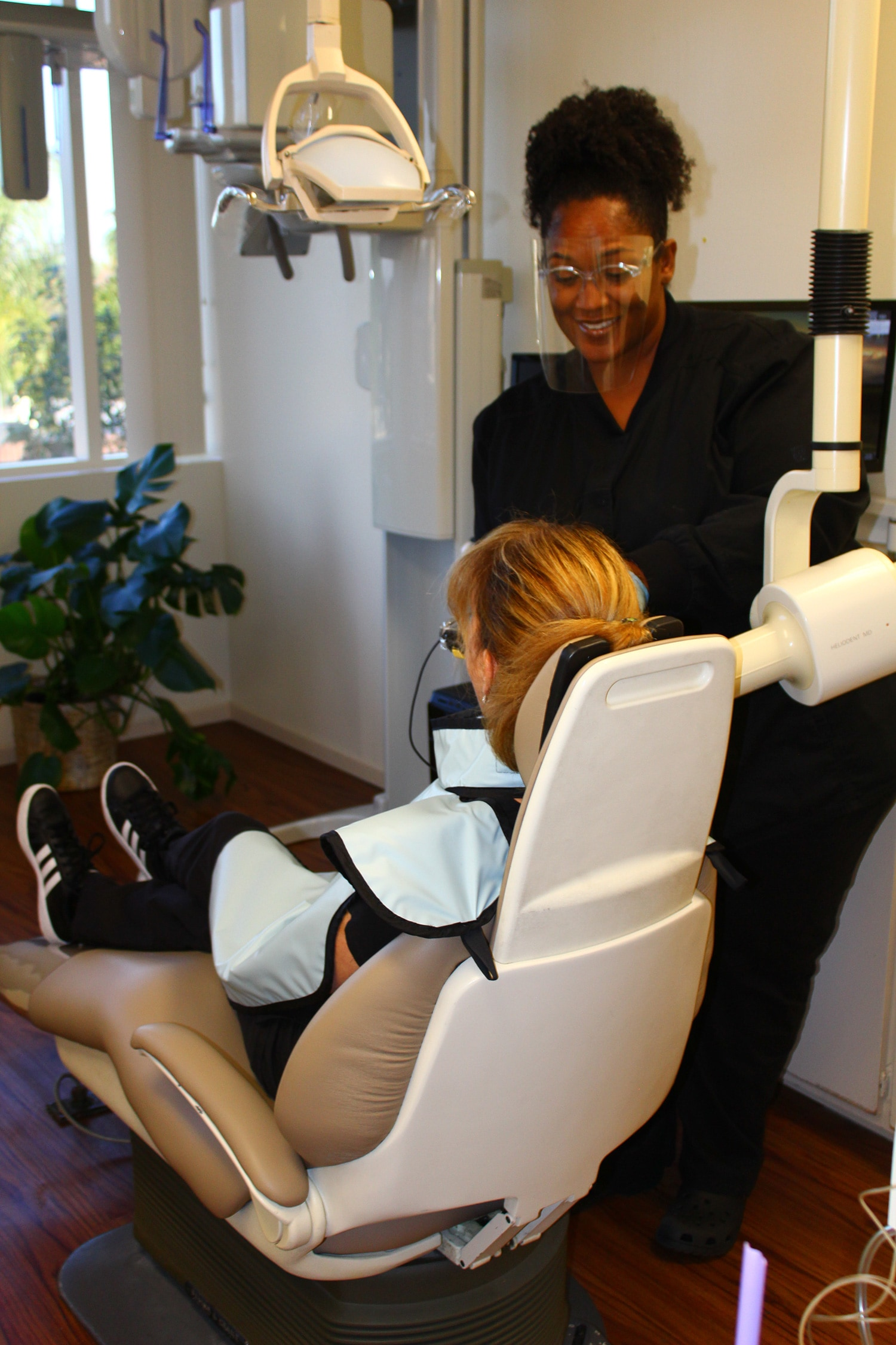 LaShon Bundy assisting a patient and Eninco dentist with root canal therapy at Encino Cosmetic Dentistry.
